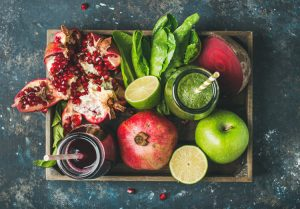 Green and purple fresh juices or smoothies with fruit, greens, vegetables in wooden tray, top view, selective focus. Detox, dieting, clean eating, vegetarian, vegan, fitness, healthy lifestyle concept
